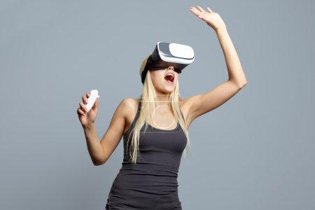 Photo pour Femme en utilisant le casque de réalité virtuelle et gesticulant mains en studio - image libre de droit
