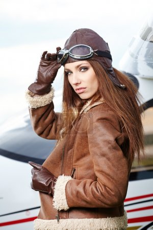 Beautiful woman pilot in front of airplane