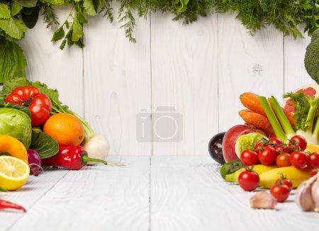 Foto de Frame with fresh organic vegetables and fruits on wooden background - Imagen libre de derechos