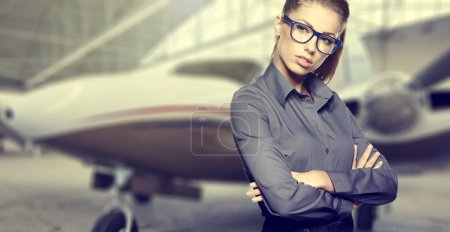 Business woman against private jet