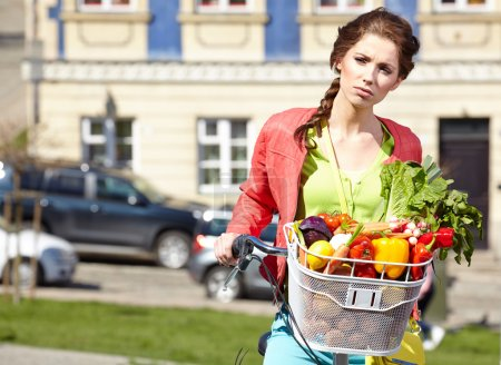 Woman with bicycle and groceries