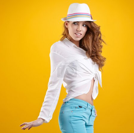 Photo for Young happy girl in hat on yellow background - Royalty Free Image