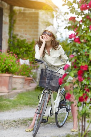 woman with retro bicycle in a garden