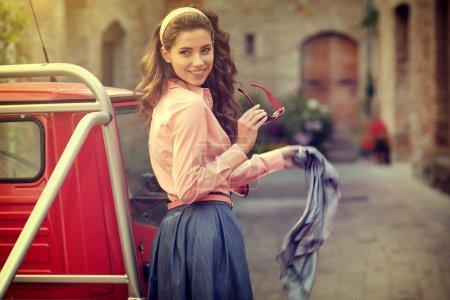 woman standing near vintage car