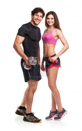 Photo for Athletic couple - man and woman with dumbbells on the white background - Royalty Free Image