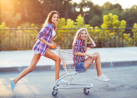 Photo for Two happy beautiful teen girls driving shopping cart outdoors, lifestyle concept - Royalty Free Image