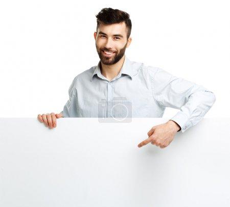 Photo pour Un jeune homme barbu montrant un panneau vierge, isolé sur fond blanc - image libre de droit