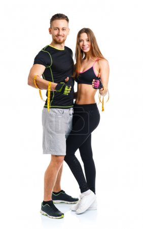 Happy athletic couple - man and woman with measuring tape on and