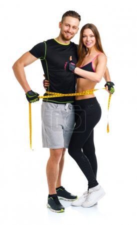 Happy athletic couple - man and woman with measuring tape on the