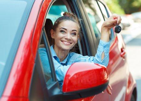 Photo pour Jeune femme joyeuse assise dans une voiture avec les clés à la main - concept Rent a car - image libre de droit