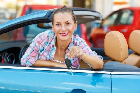Photo pour Jeune jolie femme assise dans une voiture décapotable avec les clés à la main concept d'achat d'une voiture d'occasion ou une voiture de location - image libre de droit