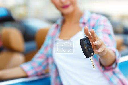 Photo pour Jeune femme debout près d'une décapotable avec les clés à la main - concept d'achat d'une voiture d'occasion ou une voiture de location - image libre de droit