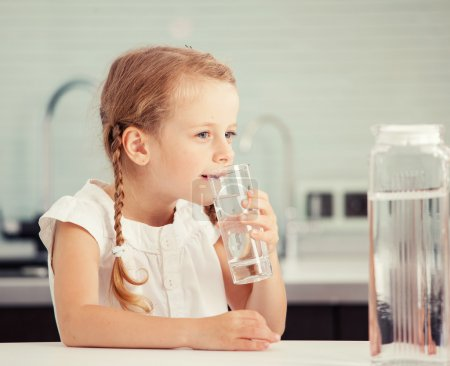 Photo for Child drinking water from glass. Happy little girl at home in kitchen - Royalty Free Image
