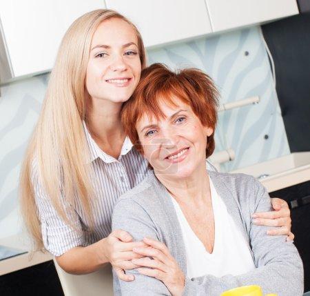 Photo pour Bonne femme adulte avec fille sur la cuisine. Famille à la maison . - image libre de droit