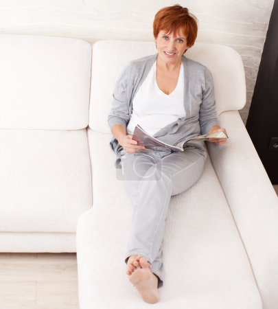 Photo for Mature woman reading magazin lying at sofa - Royalty Free Image
