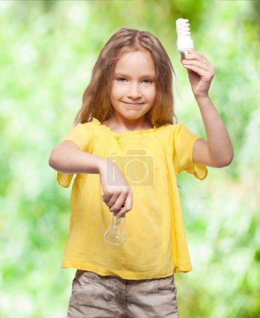 Photo pour Enfant avec ampoules. Fille tenant une lampe à incandescence à économie d'énergie - image libre de droit