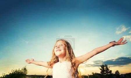 Photo pour Enfant avec bras tendus. Liberté. Fille sur un fond de ciel - image libre de droit