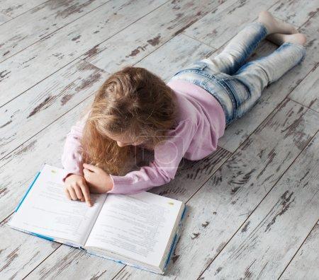 Photo pour Un livre pour enfants à la maison. Fille faire des devoirs - image libre de droit