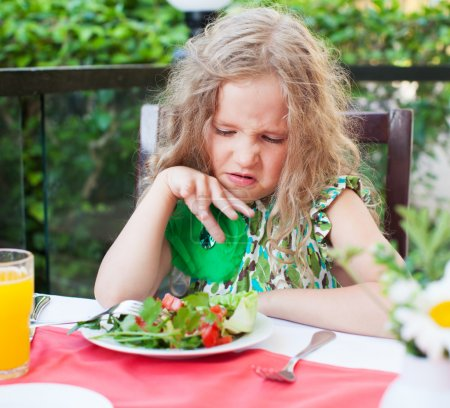 Girl does not like the food. Child with disgust lo...