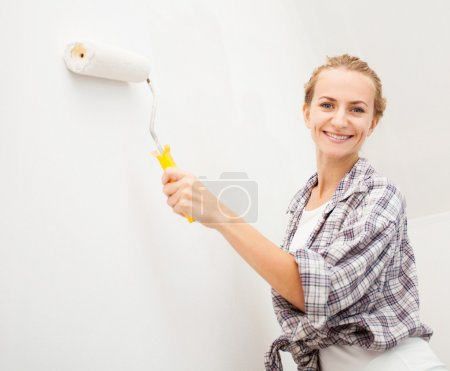 Photo for Woman doing repairs. Female paints the wallpaper roll - Royalty Free Image