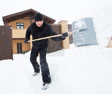 Man cleans snow shovel