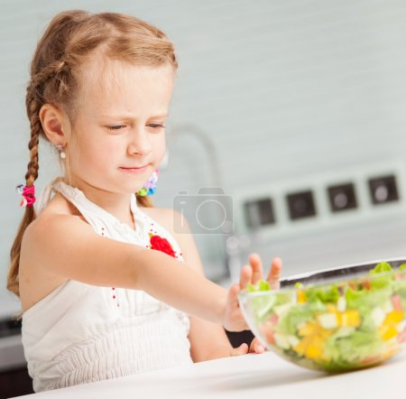 Photo for Little girl refuses to eat salad. Child looks with disgust for food - Royalty Free Image