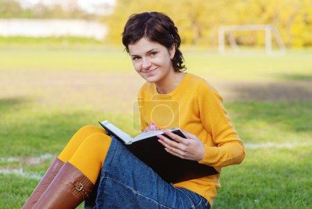 Photo pour Jeune étudiant tenant des livres sur fond d'automne . - image libre de droit