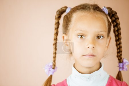 Photo for Beautiful little girl with tails close up on light brown background. - Royalty Free Image