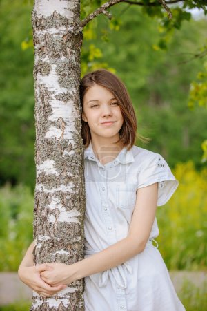 portrait of young dark-haired woman embracing birch tree
