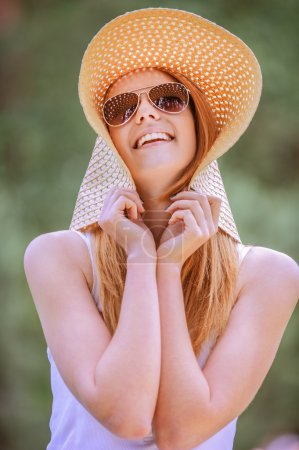 beautiful smiling young woman in wide beach hat