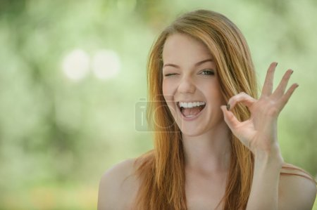 young woman lifts thumb upwards