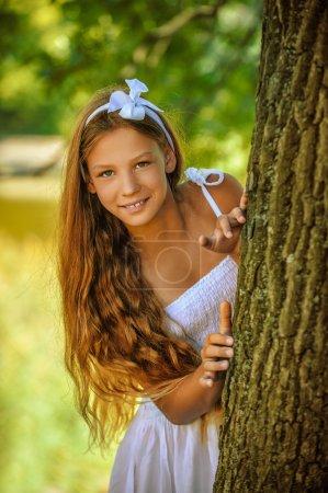 verängstigter Teenager guckt hinter Baum