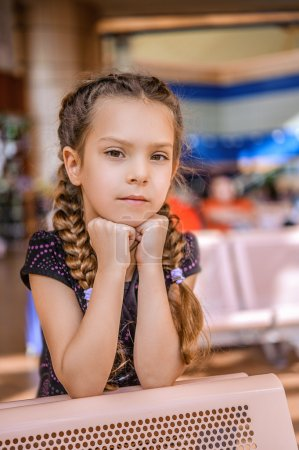 Photo for Beautiful little girl sitting at table and thinks. - Royalty Free Image