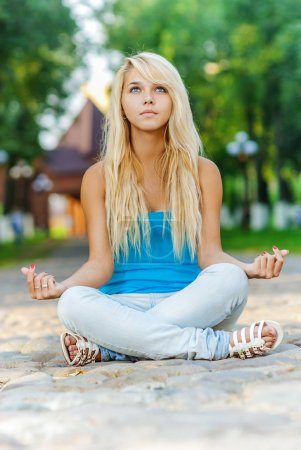 Photo for Beautiful blonde sits in lotus pose in city park. - Royalty Free Image