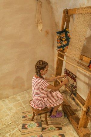 Girl sits at old loom