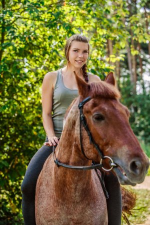 Young beautiful woman rides horse