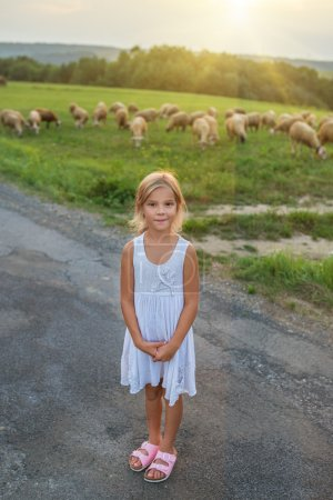 Little girl on pastures with sheep
