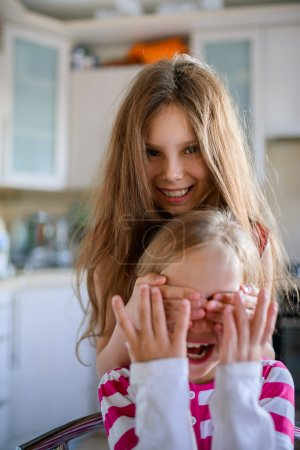 Girl closes eyes to her sister