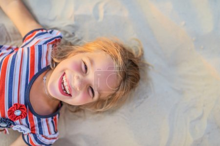 smiling little girl lies on beach sand