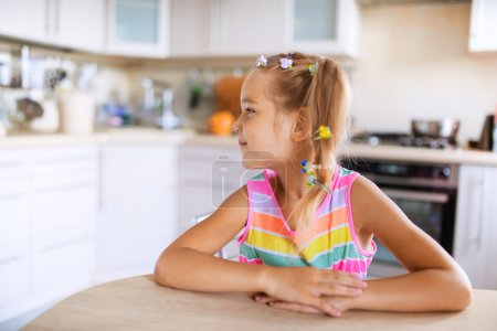 little girl sitting at table