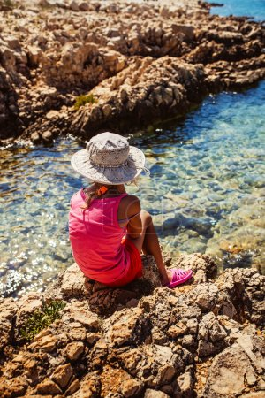 Photo for Beautiful little girl sitting on the rocky shore of the Adriatic Sea in Croatia, and looks into the distance. - Royalty Free Image