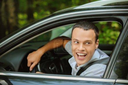 Porträt eines jungen Mannes, der Auto fährt und jemanden mit Han begrüßt