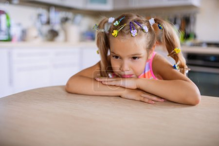 Photo for Little beautiful sad girl sits at a table in the kitchen. - Royalty Free Image