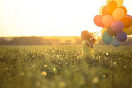 Photo for Happy girl with balloons in the field - Royalty Free Image
