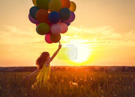 Photo pour Petite fille avec des ballons sur le coucher du soleil - image libre de droit