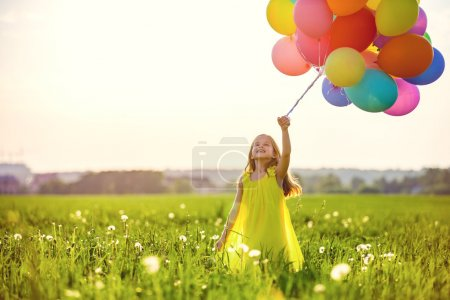 Photo for Little girl with balloons in the field - Royalty Free Image