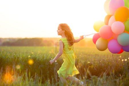 Photo pour Petite fille avec des ballons dans le domaine - image libre de droit