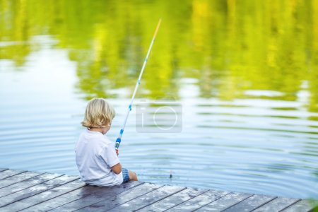 Photo for Little boy fishing on the pier - Royalty Free Image