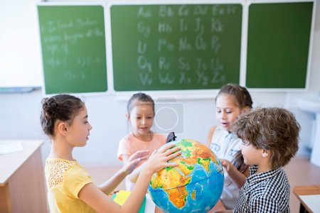 Children with globe in classroom