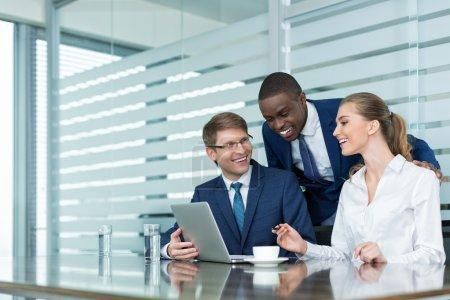 Photo pour Des hommes d'affaires souriants au bureau - image libre de droit
